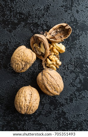 Cracked dried walnuts on black table. #705351493