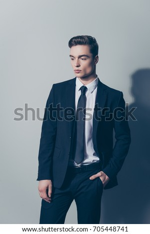 Vertical portrait of stylish confident young man in black suit posing against gray background #705448741
