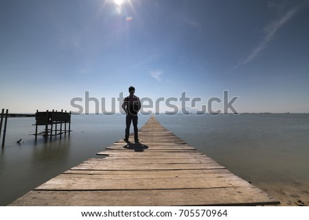 Nha Trang City, Khanh Hoa province, Vietnam - August 13, 2017: A man stands on a wooden bridge and is watching the beauty of the sea. The concept of loneliness      #705570964
