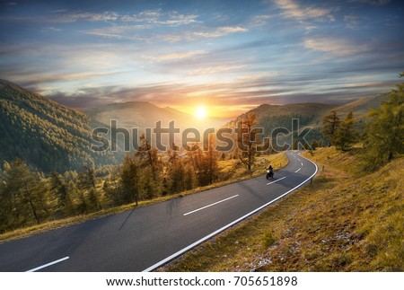 Motorcycle driver riding in Alpine highway,  Nockalmstrasse, Austria, Europe. Outdoor photography, mountain landscape. Travel and sport photography. Speed and freedom concept #705651898