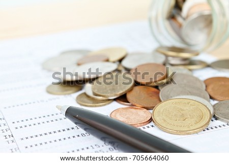 Business, finance, savings or loan concept : Coins scattered from glass jar and pen on saving account passbook or financial statement #705664060