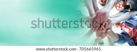 Digital composite of Low angle of creative team putting hands together and blurry teal transition #705665965