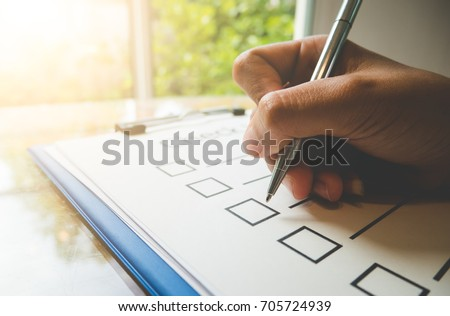 Close- up hand holding pen on check list paper and the format for filling in information in business concept,vintage style and softtone Royalty-Free Stock Photo #705724939