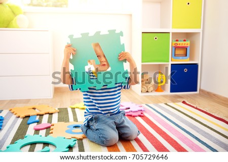 Little child playing with numbers. Boy sitting on the floor at home #705729646