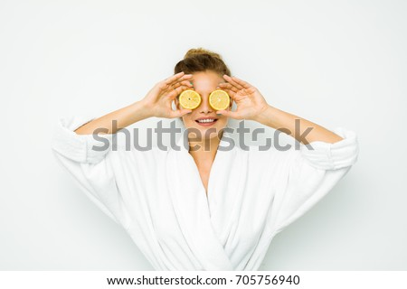 young beautiful woman standing on a white wall in bath towel playing with her favorite fruit, the lemon #705756940