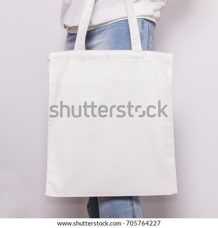 Girl in blue jeans holds blank cotton eco tote bag, design mockup. #705764227