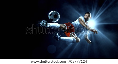 Soccer player in action on a dark background #705777124