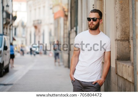 Hipster handsome male model with beard wearing white blank t-shirt with space for your logo or design in casual urban style Royalty-Free Stock Photo #705804472