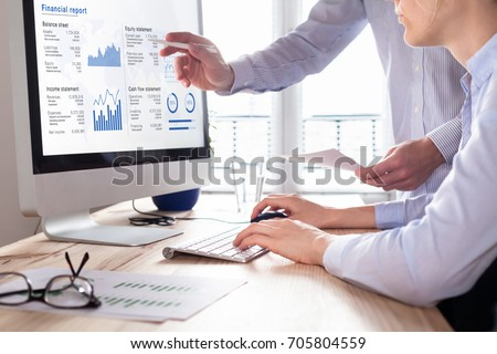 Team of consulting auditors auditing the financial report data of the company (balance sheet, income statement) on computer screen with business charts, fintech Royalty-Free Stock Photo #705804559