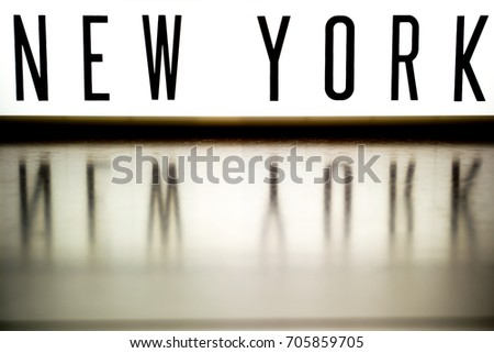 A light up board displays the phrase NEW YORK reflected on wood