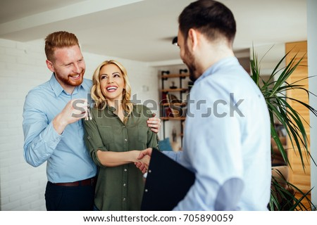 Photo of a smiling young couple thanking to the agent for the new house.