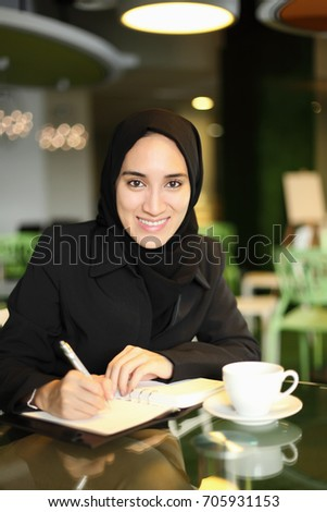 Young attractive Asian Arabic female corporate worker smiling and writing in her journal at a cafe