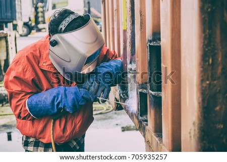 Welder worker repair the damage container wall, Industrial at the factory welding.  Worker repair container box by gas cutting and welding heavy job. worker while doing a welding with arc welder #705935257
