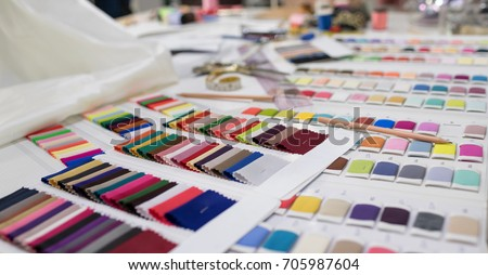 Colorful Fabric and Thread catalog on Seamstress or dressmaker work table background. Royalty-Free Stock Photo #705987604