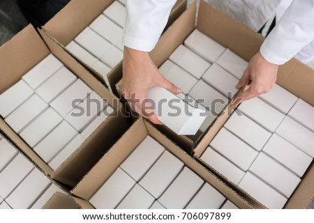 High-angle close-up view of the hands of a manufacturing worker putting packed products, in cardboard boxes before export or shipping during manual work in a cosmetics factory #706097899