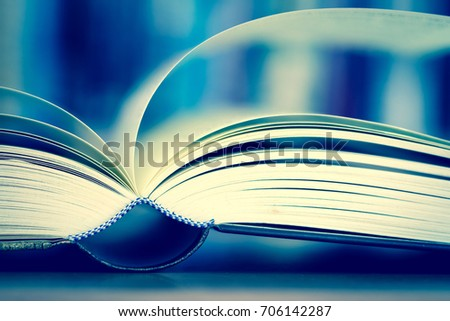 Close up opened book page with blurry bookshelf background for education and publication concept , extremely DOF with vintage retro color tone #706142287