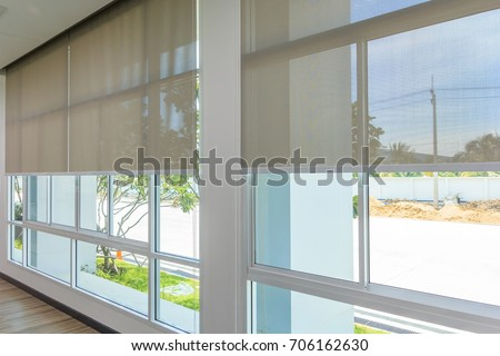 Roll Blinds on the windows, the sun does not penetrate the house. Window in the Interior Roller Blinds. Beautiful Blinds on the Window, the Sun and Heat Protection, the Perfect Windows Interior Decor Royalty-Free Stock Photo #706162630