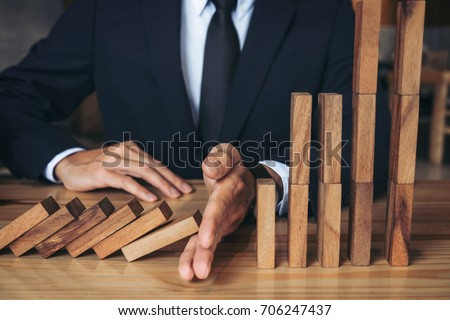 Close up of businessman hand Stopping Falling wooden Dominoes effect from continuous toppled or risk, strategy and successful intervention concept for business. Royalty-Free Stock Photo #706247437