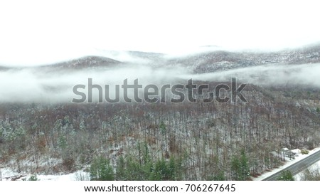 Aerial shot of a cloudy Adirondack Mountain on a snowy day. The clouds seem to cut the mountains in half. The ground is lightly covered with a fresh coat of snow. A road sneaks into the picture.