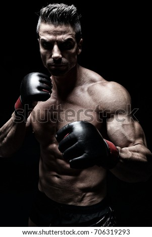 Powerful fighter posing in front of black background #706319293