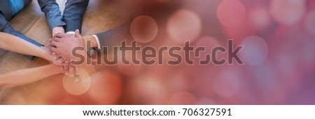 Digital composite of Overhead of business team putting hands together on table and red bokeh transition #706327591