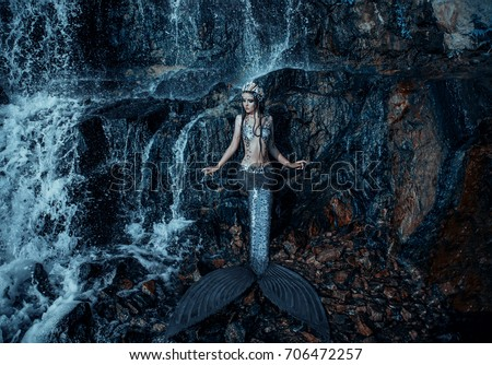 The real mermaid is resting on the ocean shore. Silver tail, the body is covered with scales. Creative colors #706472257