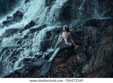 gothic real mermaid  resting on ocean shore. Wet Silver tail, the body is covered with scales. Creative costume clothes. Queen of sea, crown shells. Summer view landscape a huge waterfall rock stone #706472269