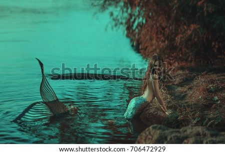 The real mermaid is resting on the ocean shore. Silver tail, the body is covered with scales. Creative colors #706472929