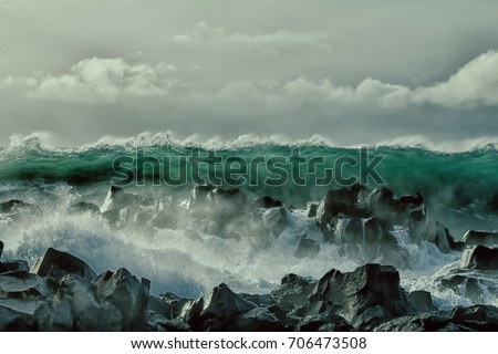 Wall of water like tsunami - turbulent waves of Pacific ocean more than 8 meters (heavy) and rugged beauty of basalt rocks (reef, shoal head). Dangerous hurricanes and cyclones becoming more frequent