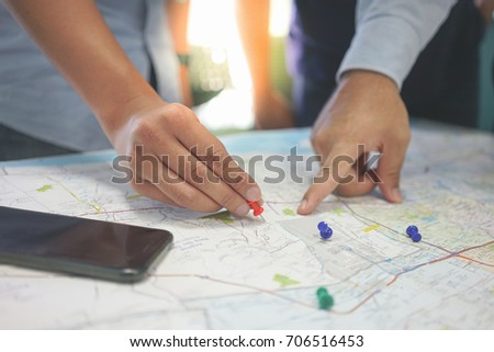 Two businessmen are talking about the target customer in the map. They hold pin in the hand and pointing finger to the area in the map. #706516453