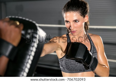 Tough resilient motivating woman at mixed martial arts gym throws a strike at practice gloves Royalty-Free Stock Photo #706702093