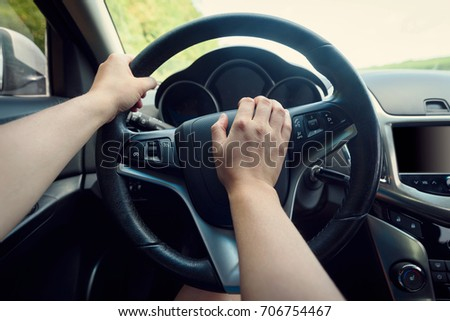 Close up of woman hand pressing the horn button while driving a car through the road. Woman driving a car with hand on horn button. Closeup woman hand holding steering wheel and honking the horn #706754467