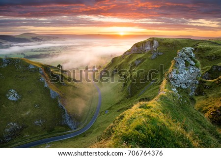 Long winding rural road leading into misty valley in the English Peak District. #706764376