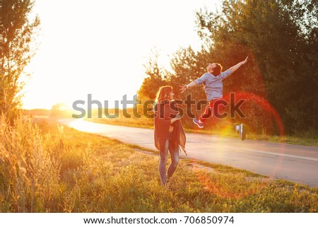 A couple at a country road. He jumps up cheerfully. She looks at him. They are fooling around. The road goes into the sunset. Love and tenderness. #706850974