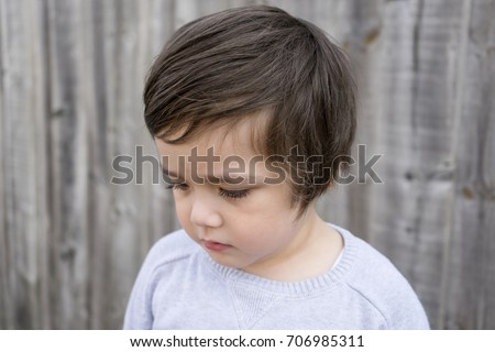 Side view portrait of little boy standing next to wooden wall with upset face and start crying, Kid crying, unhappy child concept  #706985311
