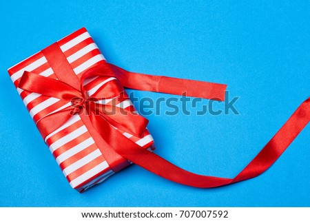 Gift in red and white packing with ribbon on a blue background. a Christmas gift #707007592