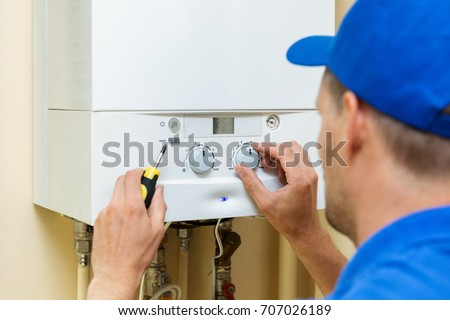 worker set up central gas heating boiler at home Royalty-Free Stock Photo #707026189