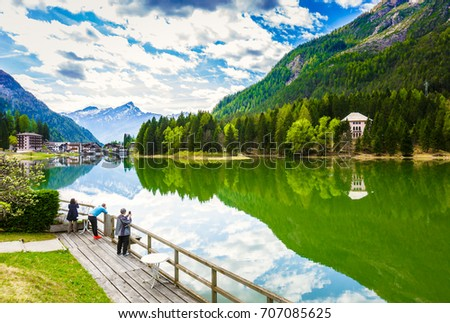 Landscape view of lake Alleghe in spring with beautiful reflection of trees and mountains of Dolomites, Italy #707085625