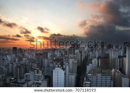 Sao Paulo, Brazil.  Beautiful dramatic sky with sun behind clouds. Sunset hour in the city. Fog and pollution around. #707118193