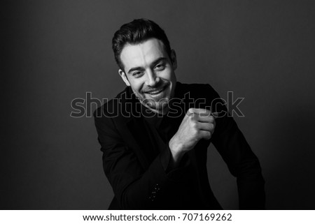 Black and white portrait of a young handsome man in a suit, smiling and looking at the camera, against plain studio background. #707169262