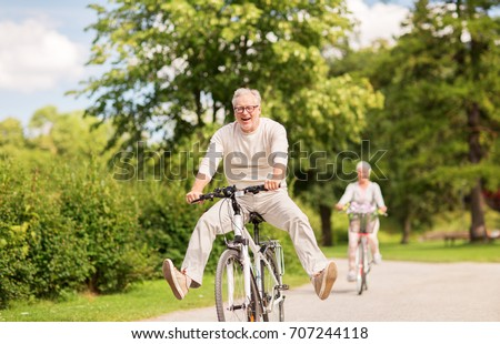 active old age, people and lifestyle concept - happy senior couple riding bicycles at summer park Royalty-Free Stock Photo #707244118