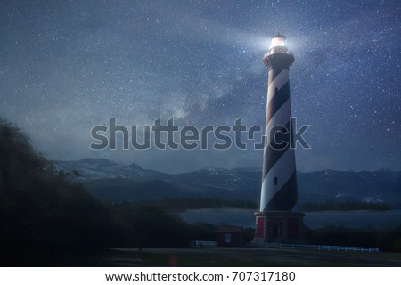 A beautiful night sky behind a shining lighthouse Royalty-Free Stock Photo #707317180