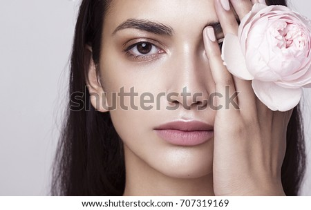 Beauty photo portrait of a young beautiful woman with a white rose in her hand hiding her eye.
