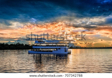 Picturesque sunset  landscape with the riverboat at Zambezi river near Livingstone in Zambia #707342788