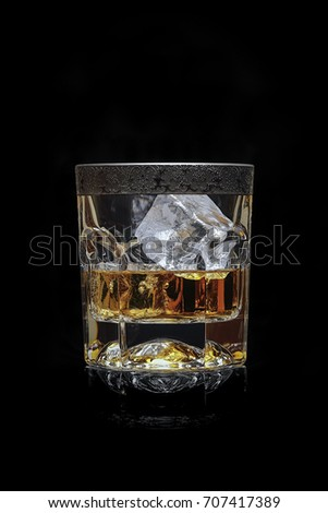 Whisky on The Rocks in Luxurious Crystal Glass on Black Background