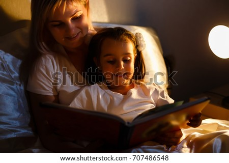 mother and child girl reading a book in bed before going to sleep #707486548