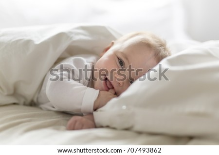 Cute happy 7 month baby girl in diaper lying and playing Royalty-Free Stock Photo #707493862