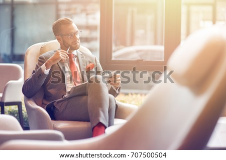 Mull it over. Confident positive thoughtful businessman sitting in the departure lounge and reading a newspaper #707500504