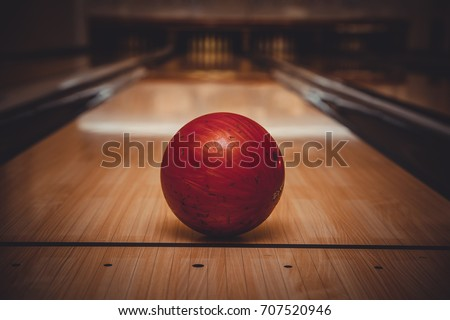 red bowling ball on the track in the bowling center