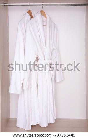 Bathrobes hanging in wardrobe #707553445
